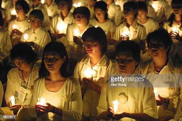 Members of the Falun Gong spiritual movement hold candles during a candlelight vigil July 19 2001 in Washington DC to mark the second anniversary of...