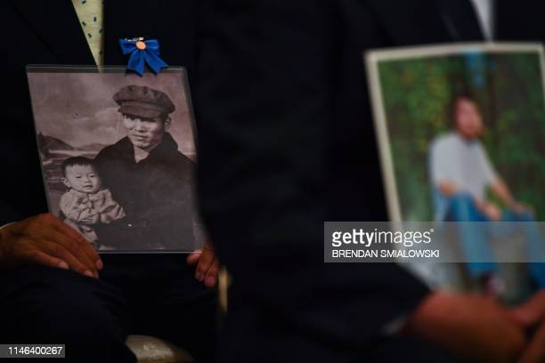 Members of the families who have had relatives abducted by North Korea, hold pictures as they listen to US President Donald Trump during a meeting at...