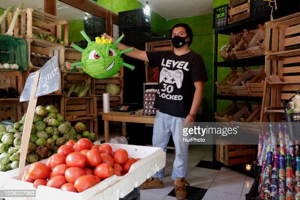 Members of the family business Pinatas Papelitos in Mexico City Mexico on July 10 2020 make and sell Coronavirus pinatas due to the health emergency...