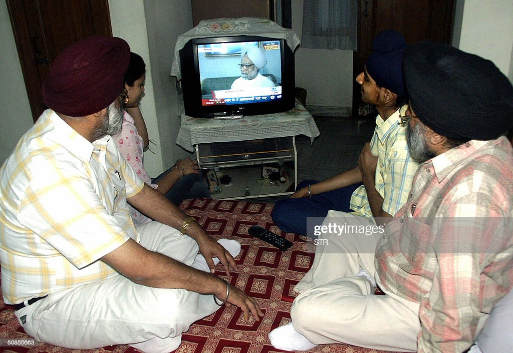 Members of the family of Indian Congress Party Senior Leader Manmohan Singh including his brothers Daljit and Surjit watch as he appears on a...