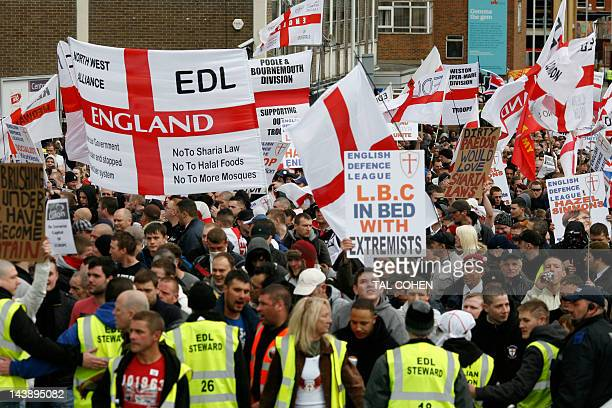 Members of the far-right English Defence League brandish placards and flags during an anti-Islam rally in Luton on May 5, 2012. The demonstration,...