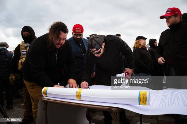 Members of the far-right group known as the Proud Boys sign a document on the grounds of the Capitol Building on January 6, 2021 in Washington, DC. A...