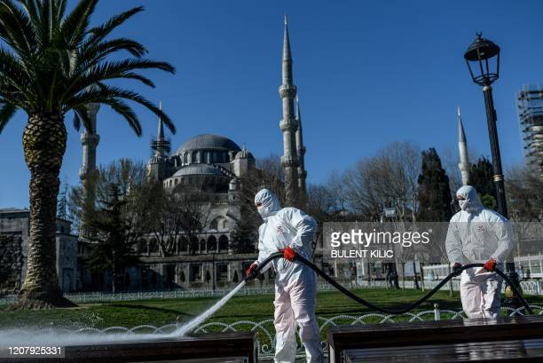 Members of the Fatih Municipality disinfect Istanbul's Sultanahmet square with the Blue Mosque seen in the backgroung to prevent the spread of the...