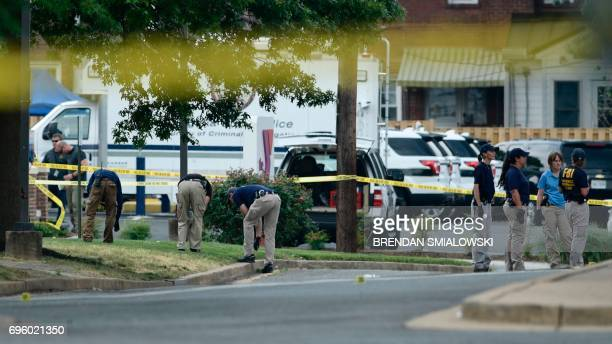 Members of the FBI collect evidences the crime scene after a shooting during a practice of the Republican congressional baseball at Eugene Simpson...