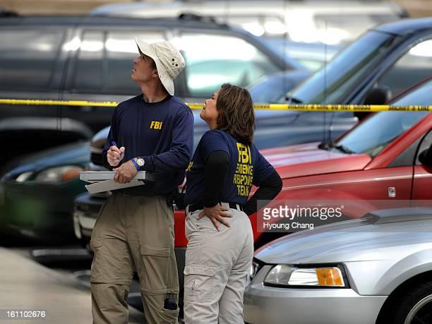 Members of the FBI evidence response team watch FBI agents raid the apartment of Najibullah Zazi at the Vistas Apartment Complex at 22959 East Smoky...