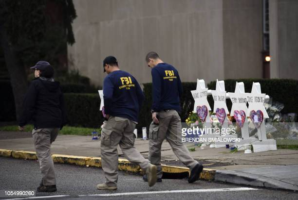 Members of the FBI walk past a memorial outside the Tree of Life synagogue after a shooting there left 11 people dead in the Squirrel Hill...