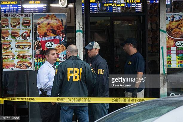 Members of the Federal Bureau of Investigation and other law enforcement officials speak outside a fried chicken store that is underneath the...