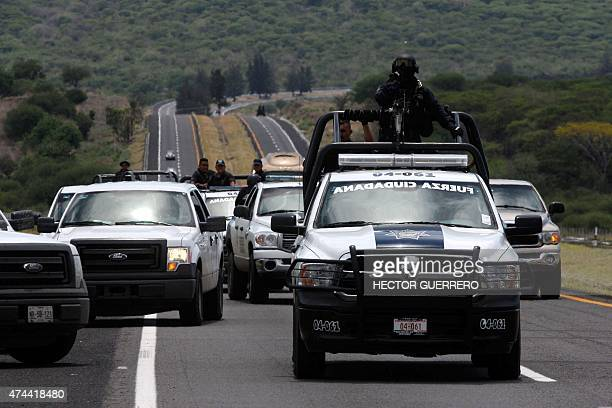 Members of the Federal police gather along the JaliscoMichoacan highway in Vista Hermosa Michoacan State on May 22 2015 near the ranch where gunmen...