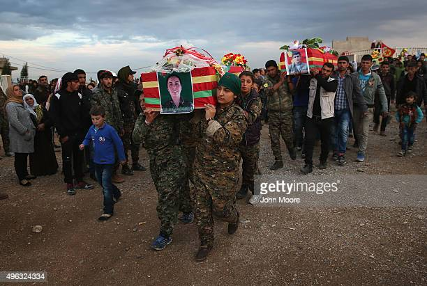 Members of the female division of the People's Protection Units carry the body of comrade Roj Adiyaman of of eight soldiers that were buried in the...