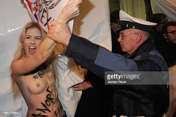 Members of the feminist group FEMEN are blocked by police during the Milan Womenswear Fashion Week on February 24 2012 in Milan Italy FEMEN is a...
