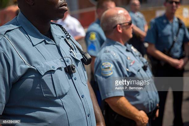 Members of the Ferguson Police department wear body cameras during a rally August 30 2014 in Ferguson Missouri Michael Brown an 18yearold unarmed...