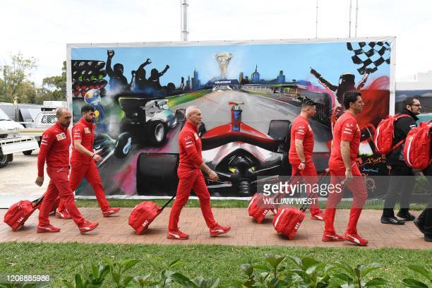 TOPSHOT Members of the Ferrari team arrive to pack up their equipment after the Formula One Australian Grand Prix was cancelled in Melbourne on March...