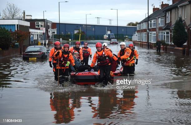 Members of the Fire and Rescue service evacuate an elderly resident to dry land from a flooded house in the Bentley suburb of Doncaster northern...