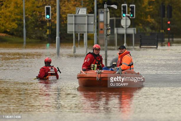 Members of the Fire and Rescue service make their way through flood water covering a flooded road Rotherham, northern England on November 8 following...