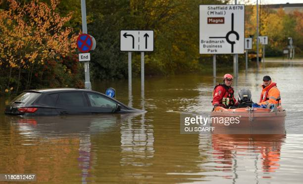 Members of the Fire and Rescue service make their way through flood water covering a flooded road Rotherham northern England on November 8 following...