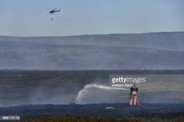 A members of the Fire and Rescue service tackles wildfires near Swineshaw reservoir in Stalybridge on June 28 2018 in Stalybridge England Around 100...