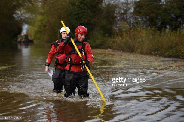 Members of the Fire and Rescue service wade through flodwater in a flooded street in the village of Fishlake near Doncaster northern England on...