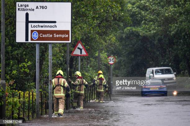 Members of the Fire Brigade are on hand to assist vehicles through flood water following torrential rain on the A760 road near to Lochwinnoch on...