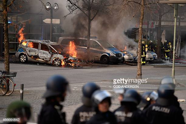 Members of the Fire Brigade attempt to put out burning Police cars on the opening day of the European Central Bank in Frankfurt am Main western...