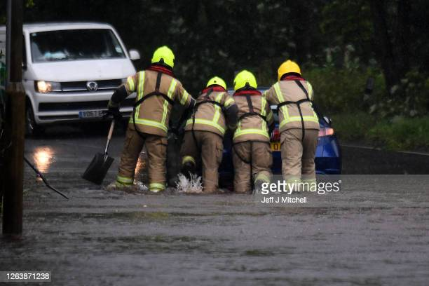 Members of the Fire Brigade push a car through flood water following torrential rain on the A760 road near to Lochwinnoch on August 2, 2020 in...