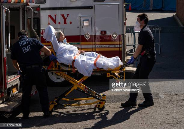 Members of the Fire Department of New Yorks Emergency Medical Team take in a patient at the emergency room of the Elmhurst Hospital Center on April...
