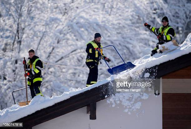 Members of the fire department remove snow from the roof of a house on January 11 2019 in Schoenau am Koenigssee Germany Exceptionally high levels of...