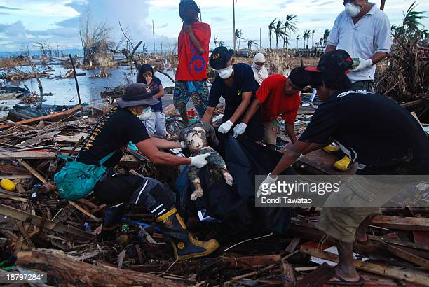 Members of the fire department retrieve bodies from the rubble in Tacloban City on November 14 2013 in Leyte Philippines Typhoon Haiyan which ripped...