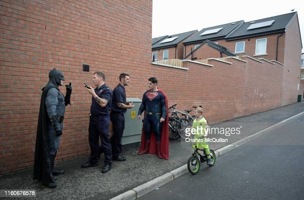 Members of the Fire Service talk with community workers dressed as comic book superheroes Batman and Superman as former Sinn Fein President Gerry...