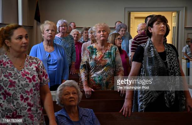 - Members of the First Baptist Church of Luverne follow a Bible verse that was projected on a screen above the pulpit during the Sunday sermon. - The...