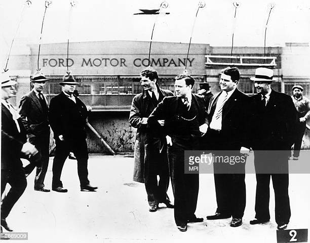 Members of the Ford Motors Service Department including Elmer Janofski approaching UAW leaders Bob Kanter Walter Reuther Richard Frankensteen and J J...