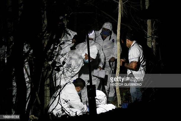 Members of the forensic service recover one of the three bodies in a mass grave found by members the State Prosecutor's Office in a forest of the...