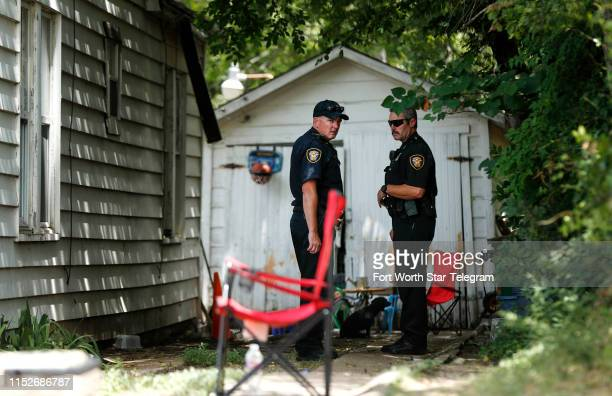 Members of the Fort Worth Police Department stand outside of the east Fort Worth Texas home where two children were shot on June 27 when another...