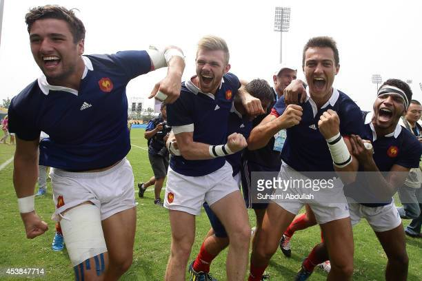 Members of the France men's rugby team celebrate after defeating Argentina to win the gold medal at the Rugby Sevens Final on day four of the Nanjing...