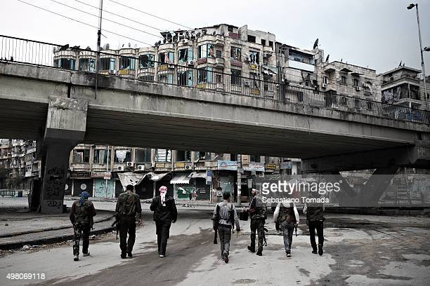 Members of the Free Syrian Army walk the abandoned street go Aleppo Syria October 27 2013