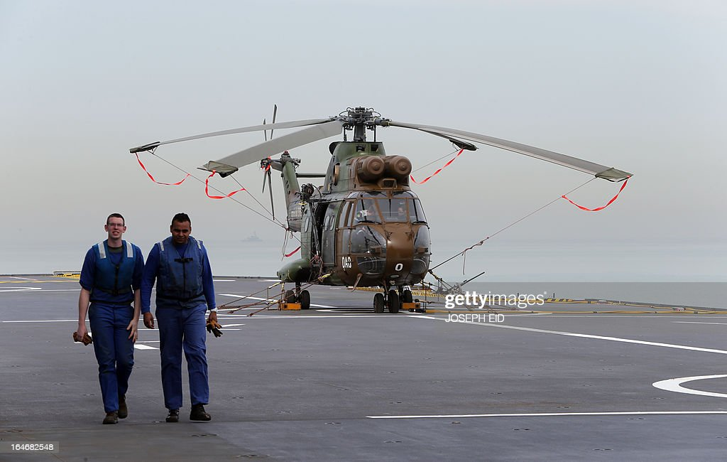 Members of the French air force walk near a helicopter on BPC Tonnerre assault helicopter carrier as they take part in sea and land war games with the Lebanese Army at the bay of Jounieh, north of Beirut, on March 26, 2013.