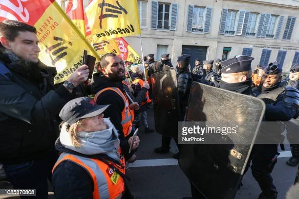 Members of the French antiriot police CRS stand guard in front of protesters in the streets of Versailles outside Paris on January 21 during a rally...