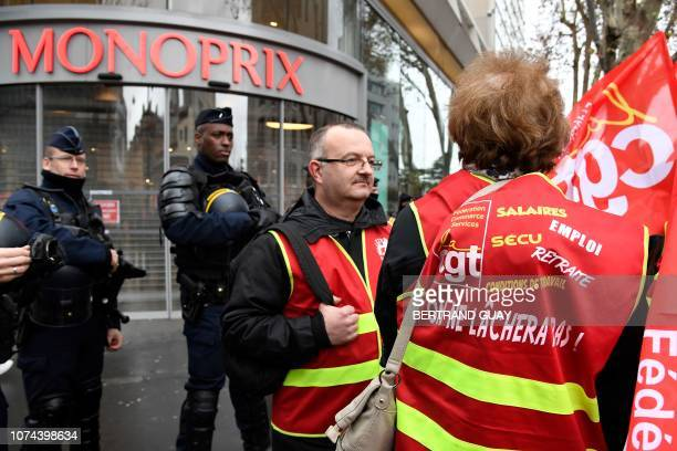 Members of the French antiriot police CRS stand guard in front of the entrance of the Monoprix store in Beaugrenelle southern Paris on December 19...