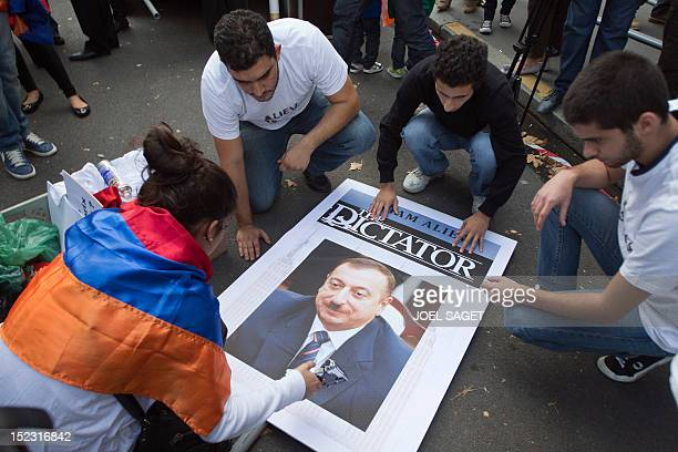 Members of the French Armenian community prepares a poster showing a portrait of Azerbaijani President Ilham Aliev in front of the Embassy of...