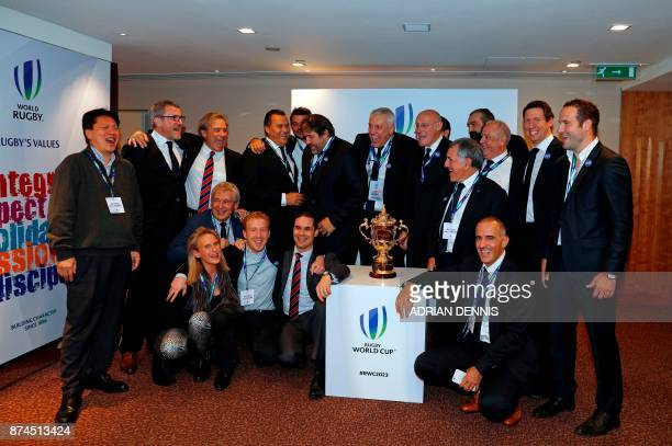 Members of the French bid including President of the French bid Claude Atcher and French rugby President Bernard Laporte pose with the trophy after...