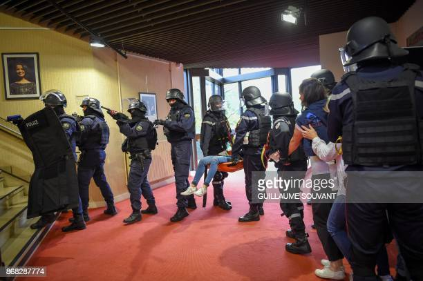 Members of the French Departmental Service of Fire and Rescue framed by French Police officers evacuate a wounded woman on a stretcher during an...