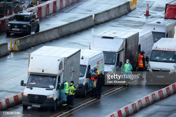 Members of the French Federation of Rescue and First Aid and the French Fire Service swab drivers to test for Covid-19 on December 24, 2020 in Dover,...