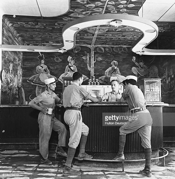 Members of the French Foreign legion are served beer over the counter at an officers' bar | Location Near Sidi bel Abbes Algeria