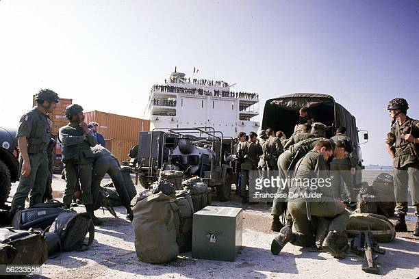 Members of the French Marine contingent of the Multinational Force secure their equipment by a truck on the quayside as they prepare to embark on the...