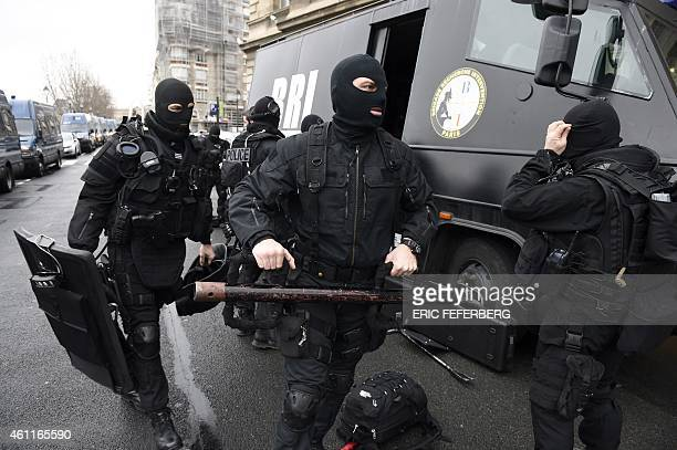 Members of the French national police intervention group prepare their gears before leaving on operation in front of Paris' police headquarters on...