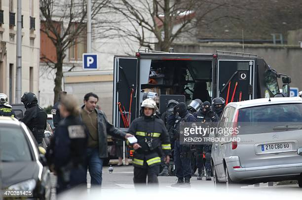 Members of the French police Brigades de Recherche et d'Intervention unload gear from a truck near an apartment where four suspected armed robbers...