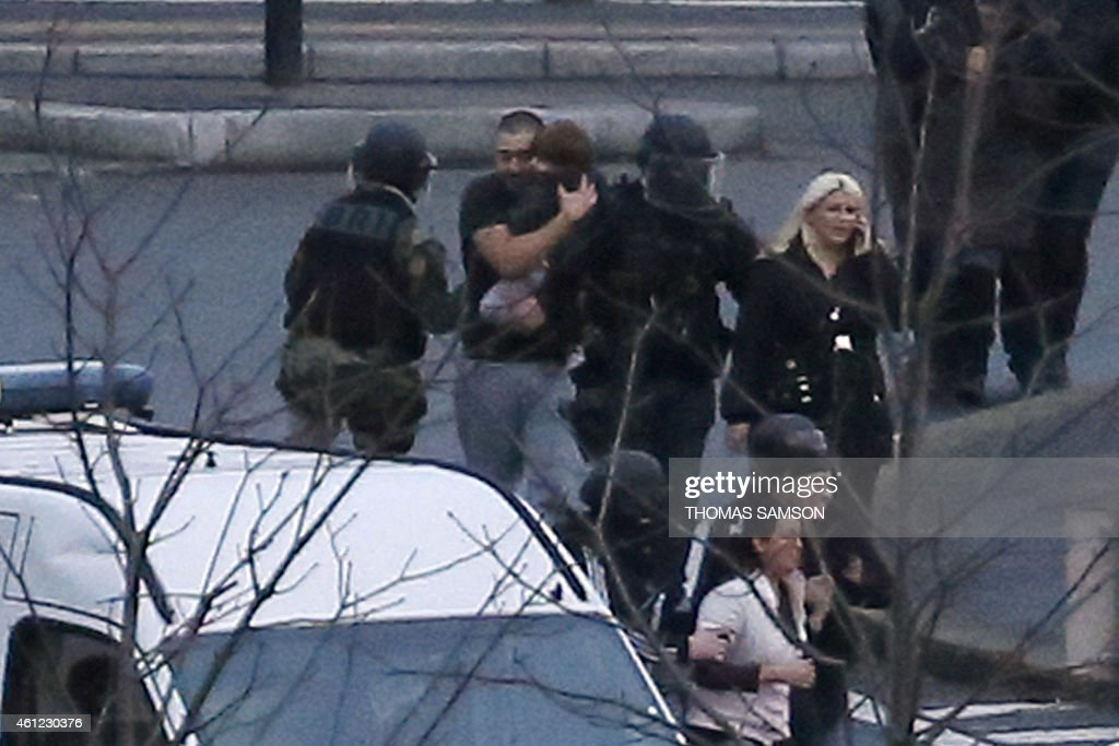 Members of the French police special forces evacuate hostages including a child (C) after launching the assault at the Hyper Cacher Kosher grocery store in Porte de Vincennes, eastern Paris, on January 9, 2015 where at least two people were shot dead on January 9 during a hostage-taking drama at a Jewish supermarket in eastern Paris, and five people were being held, official sources told AFP. Several hostages were freed after French commandos stormed a Jewish supermarket in eastern Paris where an assailant was holed up on January 9. After several explosions, police stormed the shop in Portes de Vincennes and everal hostages exited the store shortly afterwards and were taken to safety.