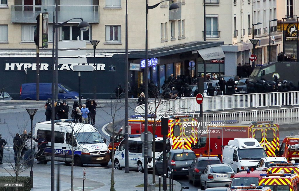 Members of the French police special forces launch the assault and evacuate the hostages at a kosher grocery store in Porte de Vincennes, eastern Paris, on January 9, 2015 where at least two people were shot dead on January 9 during a hostage-taking drama at a Jewish supermarket in eastern Paris, and five people were being held, official sources told AFP.