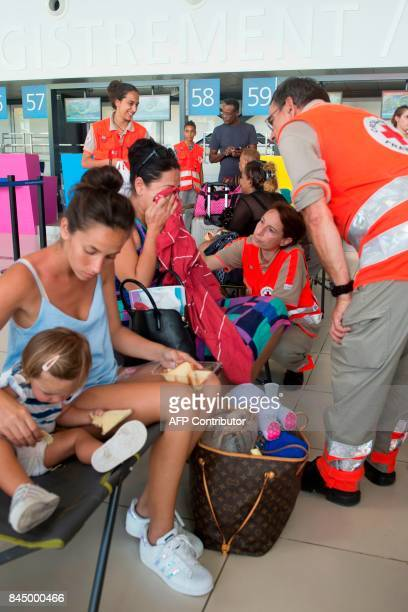 Members of the French Red Cross assist families who were evacuated from the island of Saint Martin that has been ravaged by Hurricane Irma on...