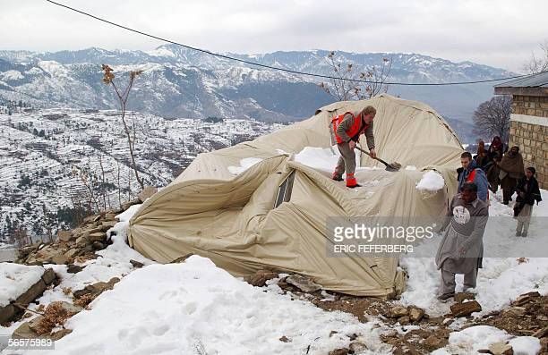 Members of the French Red Cross remove snow from the top of a tent they use as a basic health unit after it collapsed under the weight of the snow 12...