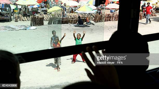 Members of the French team wave to people on the street on the way to Port Moresby Nature Park on November 18, 2016 in Port Moresby, Papua New Guinea.